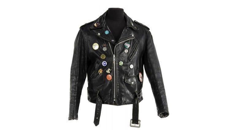 """A black leather motorcycle jacket owned by Frank Zappa. A label that reads """"Perfecto Schott Bros"""" is present. Size 46. The jacket is customized with a collection of pins. Zappa was photographed wearing the jacket with conductor Joel Thome while promoting the music of Edgard Varèse at the New York Palladium on April 16, 1981."""